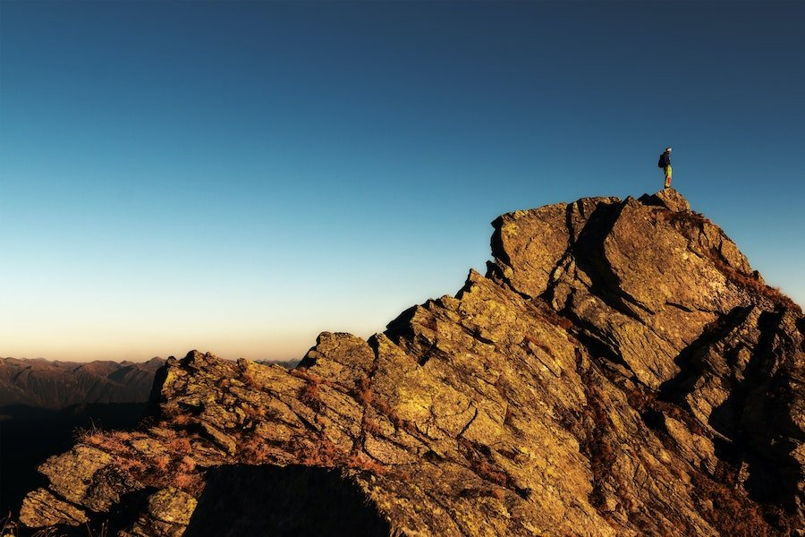 man-standing-on-top-of-rock-at-daytime-673018